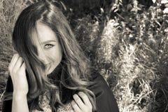 Красивая женщина с голубыми глазами, длинными коричневыми волосами и клобуком в взглядах древесин камера стоковое фото rf