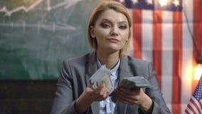 Красивая женщина с деньгами Серьезная бизнес-леди считая деньги на фоне американского флага сток-видео