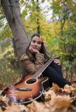 Красивая женщина с ее гитарой Стоковое Фото