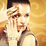 Красивая женщина с золотыми ногтями и красивое кольцо золота Стоковые Фотографии RF