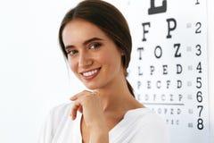 Красивая женщина с диаграммой испытания глаза на офисе офтальмологии Стоковое Изображение RF