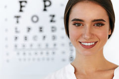 Красивая женщина с диаграммой испытания глаза на офисе офтальмологии Стоковые Изображения