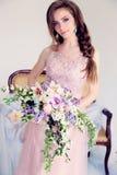 Красивая женщина с длинными темными волосами в элегантном платье представляя среди цветков Стоковые Фотографии RF