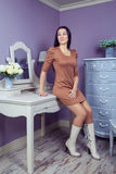 Красивая женщина с коричневым платьем и длинными черными волосами в ее комнате около ее таблицы шлихты представляя перед партией Стоковое Изображение RF