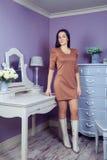 Красивая женщина с коричневым платьем и длинными черными волосами в ее комнате около ее таблицы шлихты представляя перед партией Стоковые Фото