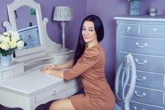 Красивая женщина с коричневым платьем и длинными черными волосами в ее комнате около ее таблицы шлихты представляя перед партией Стоковая Фотография