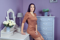 Красивая женщина с коричневым платьем и длинными черными волосами в ее комнате около ее таблицы шлихты представляя перед партией Стоковое Изображение