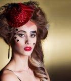 Красивая женщина с красивым составом и hairdo в маленькой красной шляпе с большими губами с сердцами на праздник стороны Valentin Стоковые Изображения