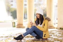 Красивая женщина с крышкой используя телефон в улице стоковое изображение