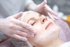 Красивая женщина с лицевой маской на салоне красоты стоковые фотографии rf