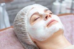 Красивая женщина с лицевой маской на салоне красоты стоковая фотография rf