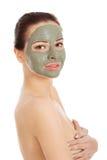 Красивая женщина с маской ухода за лицом глины Стоковое Фото
