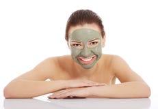 Красивая женщина с маской ухода за лицом глины Стоковые Фото
