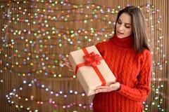 Красивая женщина с подарком рождества на запачканной предпосылке светов Стоковое Фото