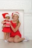 Красивая женщина с ребенком в костюмах Санты Стоковое Изображение