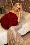 Красивая женщина с светлыми волосами в роскошных одеждах представляя с Стоковые Изображения