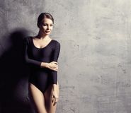 Красивая женщина с совершенным телом Девушка представляя и танцуя в купальнике Фото студии над конкретной предпосылкой Стоковые Изображения RF