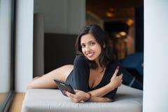 Красивая женщина с совершенным телом в черном bodysuit лежа на тюфяке около большого окна на каникулах стоковые фото