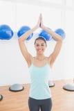 Красивая женщина с соединенными руками в студии фитнеса Стоковые Изображения