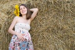 Красивая женщина с солнцецветами приближает к стогу сена - красота и мода Стоковые Фотографии RF