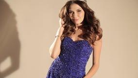 Красивая женщина с темными волосами в роскошном платье и драгоценной кроне представляя в студии акции видеоматериалы