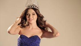 Красивая женщина с темными волосами в роскошном платье и драгоценной кроне представляя в студии видеоматериал