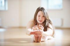Красивая женщина с улыбкой с wink практикует paschimottanasana asana йоги - усаженный передний загиб в студии йоги Стоковое Изображение