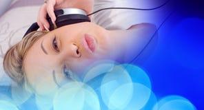 Красивая женщина слушая к светам музыки defocused голубым Стоковая Фотография