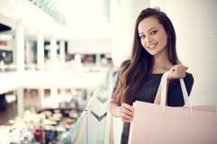 Красивая женщина с хозяйственными сумками в большом моле Стоковые Фотографии RF