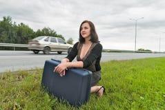 Красивая женщина с чемоданом ждет на дороге Стоковые Изображения RF
