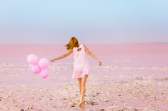 Красивая женщина с baloons на розовом озере соли стоковые фото