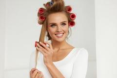 Красивая женщина с Curlers волос, роликами волос на здоровое курчавом Стоковое Изображение RF