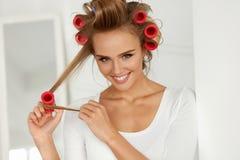 Красивая женщина с Curlers волос, роликами волос на здоровое курчавом Стоковое фото RF