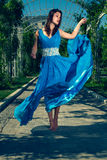 Красивая женщина танцуя barefoot в длинном голубом платье Стоковая Фотография