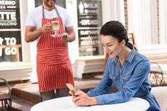 Красивая женщина тратя время в кофейне Стоковое фото RF