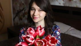 Красивая женщина усмехаться удлиняет вне цветет - тюльпаны к камере акции видеоматериалы