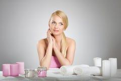 Красивая женщина усмехаясь за таблицей с свечами и полотенцами Стоковые Изображения