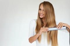 Красивая женщина утюжа длинные прямые волосы с раскручивателем Стоковое Изображение RF