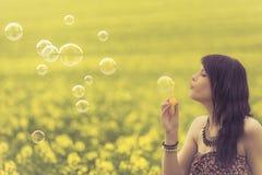 Красивая женщина дуя много пузырей мыла в природе лета Стоковое Фото