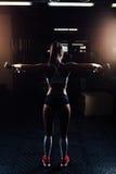 Красивая женщина фитнеса с поднимаясь гантелями стоковое изображение