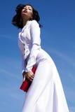 Красивая женщина (фотомодель) представляя в белом платье Стоковая Фотография