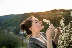 Красивая женщина черных волос наслаждаясь зацветая деревом Стоковые Фото