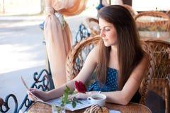 Красивая женщина читая газету в кафе Стоковое Изображение