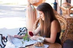 Красивая женщина читая газету в кафе Стоковые Изображения RF