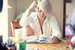 Красивая женщина читая книгу дома сидя на таблице рядом с огромным окном на солнечный теплый день Стоковое Изображение