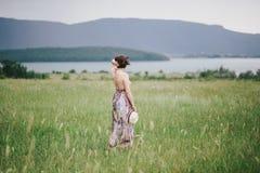 Красивая женщина hippie представляя на зеленом поле с горами на предпосылке Стоковые Изображения RF