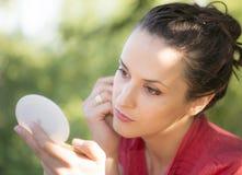 Красивая женщина loking в ее карманном зеркале Стоковое фото RF