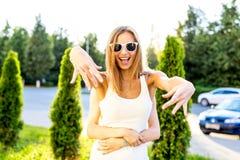 Красивая жизнерадостная девушка, развевая оружия, с его подругой за наслаждаться вашими каникулами, имеющ лето потехи расслабляющ Стоковая Фотография