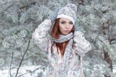 Красивая жизнерадостная милая рыжеволосая девушка в крышке и шарфе играет с снегом в красивой фее леса стоковые изображения rf