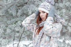Красивая жизнерадостная милая рыжеволосая девушка в крышке и шарфе играет с снегом в красивой фее леса стоковые фотографии rf